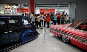 Visitors stand in front of 1939 Chevrolet Master Deluxe, named Gangster Squad '39, left, and Jesse Valadez's Gypsy Rose, a customized 1964 Chevrolet Impala, during an exhibition titled The High Art of Riding Low at the Petersen Automotive Museum in Los Angeles in 2017.
