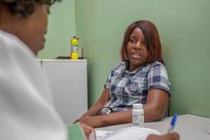 Domingas Manuela Augusto António speaks to a nurse