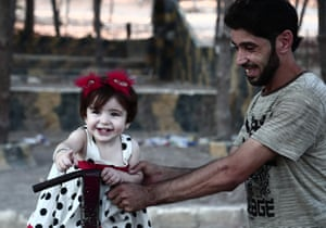 A displaced man plays with a girl in Afrin, Syria