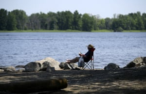 A woman reads in the shade along the Ottawa River in Ottawa