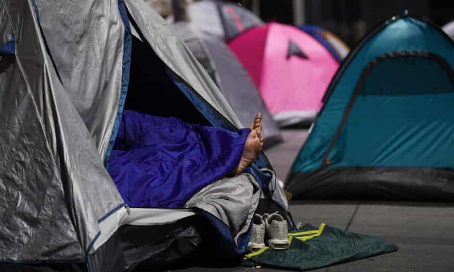 A pair of feet stick out of a tent used by a homeless person in Sydney's Martin Place,
