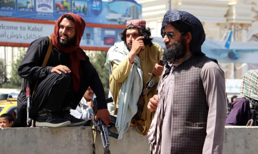Taliban fighters stand guard outside Hamid Karzai international airport on Tuesday.