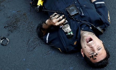 A police officer lies injured after attempting to detain a protester smearing paint on the Black Lives Matter mural.