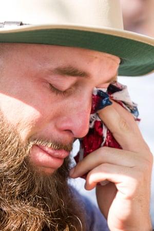 A man dabs away tears