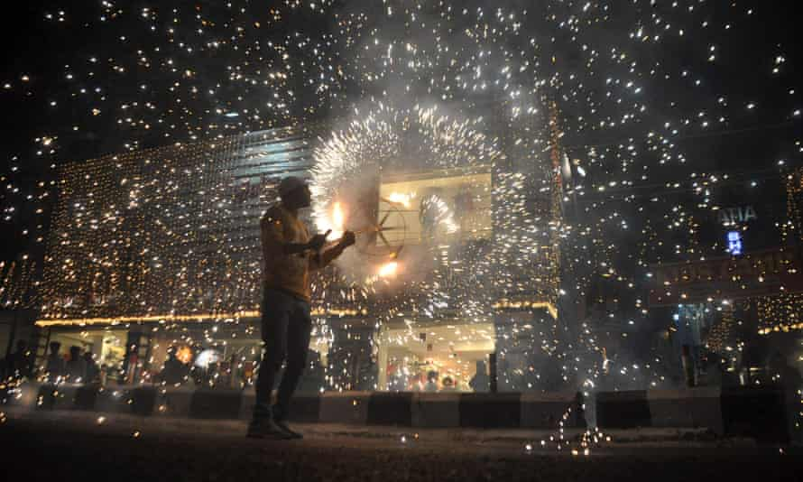 An Indian worker sets off firecrackers during a fireworks display at a local marketplace on the eve of Diwali festival in Jammu.