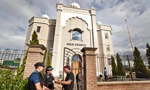 Police officers chat with a worshipper outside the Gurdwara Sahib, Leamington Spa