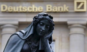 A statue next to the logo of Germany's Deutsche Bank in Frankfurt, Germany