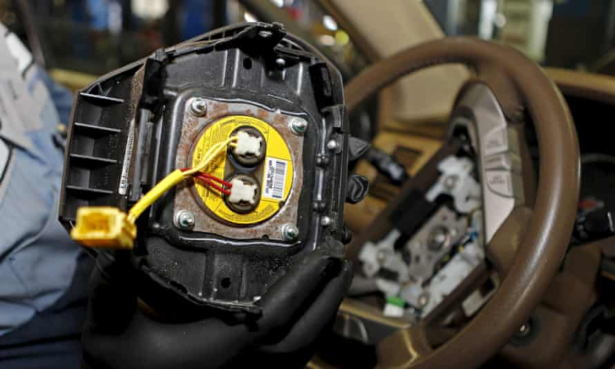 Technician holding a recalled Takata airbag inflator.