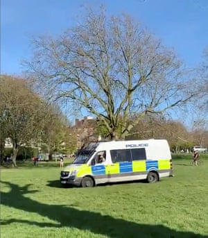 Police officers drive a vehicle through Peckham Rye Park to instruct people not to sunbathe in London yesterday.