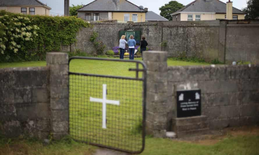 People stand at the site of a mass grave for children who died in the Tuam mother and baby home, County Galway