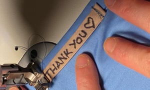 Sarah Featherstone from Sheffield sews a 'thank you' message into some handmade scrubs