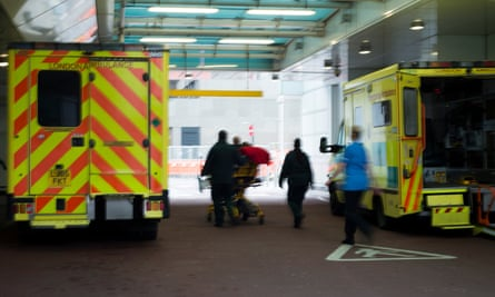 Ambulances parked outside a London hospital as NHS staff transport a patient on a gurney
