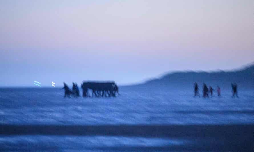 Migrants carry a boat on the beach at Gravelines, near Dunkirk