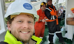 Reverend Dennis Woodward with two Filipino seafarers in the background