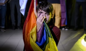 A man sits draped in a rainbow flag in a nightclub in Bucharest, Romania, after hearing of the partial voter turnout.