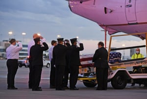 Ambulnz paramedics and Aurora firefighters salute as the casket carrying the body of paramedic Paul Cary is removed from a plane at Denver International Airport.