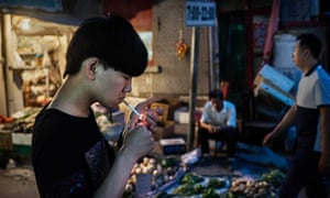 A man smokes in the street in Beijing, China