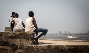 A group of children sit on the shores of the Congo river in Brazzaville looking across to Kinshasa