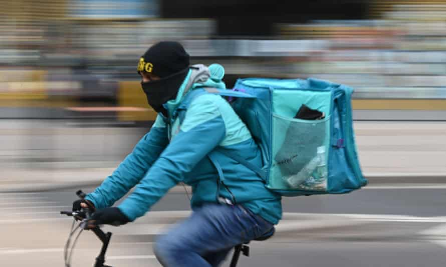 Deliveroo rider cycles through central London
