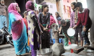 People collect water from a hand pump in the Azadpur area of north Delhi