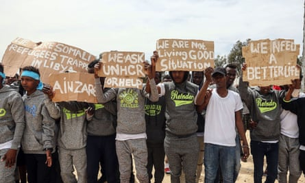 Migrants hold placards during the visit of António Guterres, the UN secretary general, to Ain Zara detention centre for migrants in the Libyan capital Tripoli