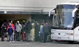 Migrants wait to board a bus to leave the Castelnuovo di Porto centre