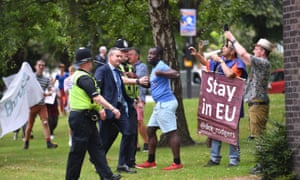 Police officers watch protesters as Boris Johnson arrives at West Midlands Police's learning and development centre, Birmingham