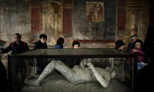 Tourists look at a body cast during their visit the archeological site of Pompeii