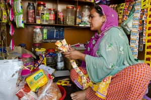 Farida Begum sorts goods at a stall she recently opened on the outskirts of Lucknow