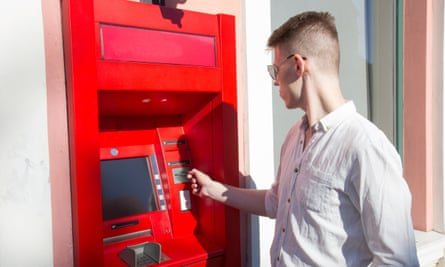 young man student withdrawing money from a bank cash point
