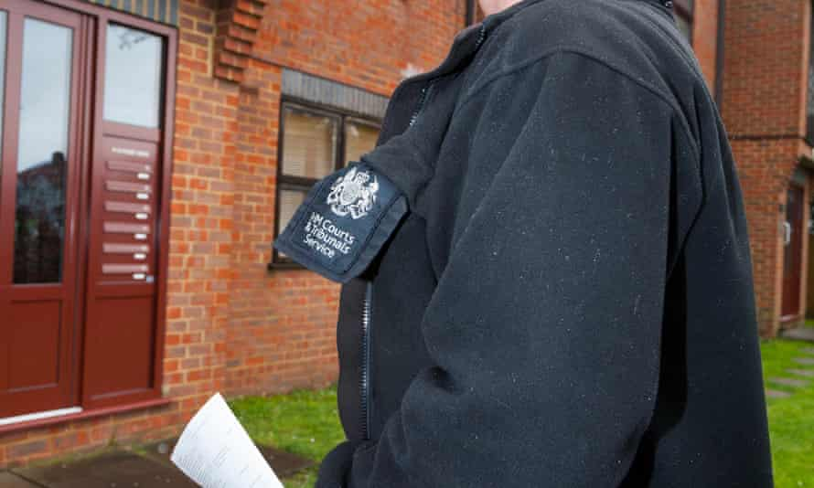 An HM Courts & Tribunals Service court bailiff serving an eviction warrant notice before the pandemic.