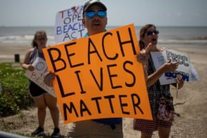 Local residents hold signs in protest of closed beaches on the 4th of July amid the global outbreak of coronavirus in Galveston, Texas, USA on 4 July, 2020.
