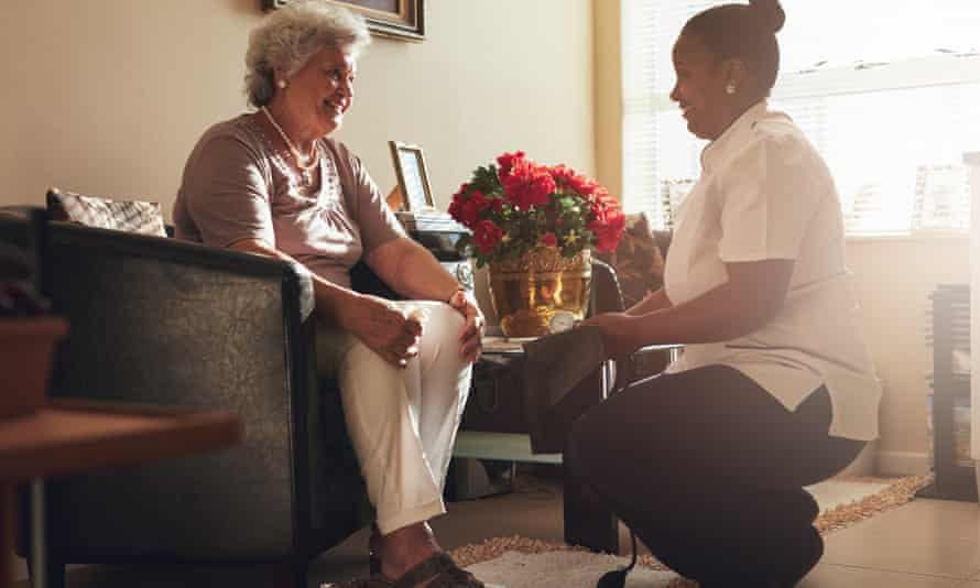 An elderly patient receives care at home, but lower budgets have led to reduced services.