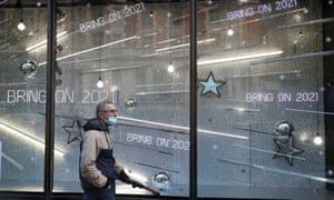 A man walking past the Christmas window display in a shop in London today.