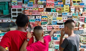 Young Brazilians look at a social art installation depiction of a favela.