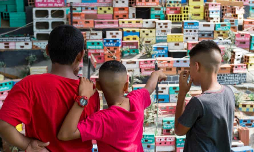 Young Brazilians in Rio de Janeiro look at an art installation depicting a favela.