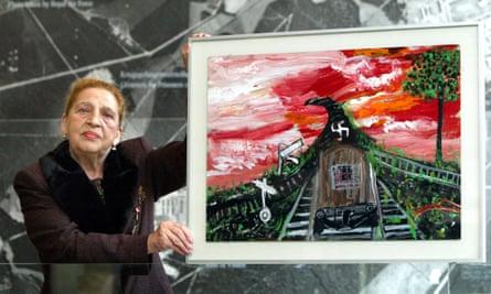 Ceija Stojka holding up painting