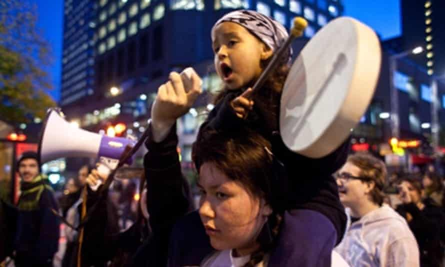 A girl plays the drums as she sings a traditional First Nations song during the demonstration on Saint Catherine street, downtown Montreal in support of the Mikmaq people of Elsipogtog First Nations in New Brunswick.
