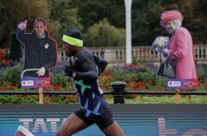 Shura Kitata runs past cardboard cut-outs of the Duke of Cambridge and the Queen.