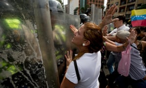 Demonstrators argue with police blocking them from reaching the headquarters of the National Electoral Council in Caracas on Wednesday