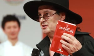 Marc Veyrat holding a Michelin guide in 2018, when La Maison des Bois was awarded the maximum three stars.