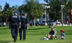 uniformed police walk by a father and small child in a park