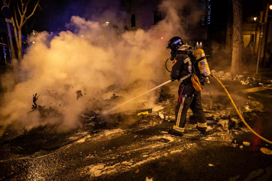 A fireman extinguishes a burning barricade in Barcelona