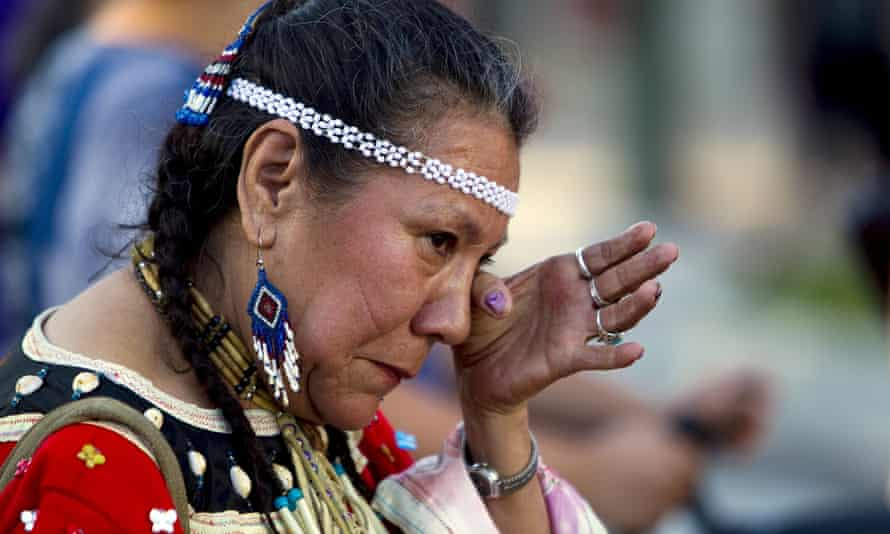 Residential school survivor Patricia Tucknaow wipes away a tear while walking to honour fellow survivors in Vancouver.