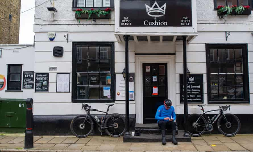 A man sits outside a closed pub in Eton, Berkshire