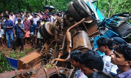 The tangled wreckage of a minibus is pictured as onlookers gather at an accident scene in Chelakkad, in the Malappuram district of India's Kerala state