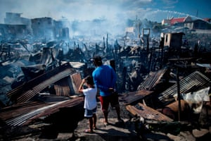 Residents look at destroyed houses after a fire engulfed a slum area in Navotas, Philippines