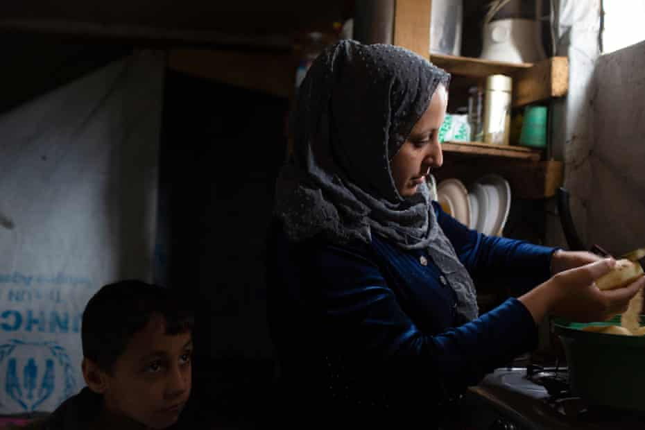 Zuhur Al Hussein, Nada's mother, peels potatoes, watched on by one of her sons