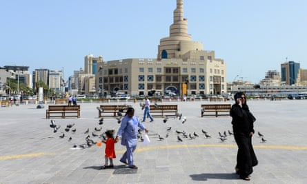 Qatari woman with housemaid in front of the Spiral Mosque in Doha, Qatar.