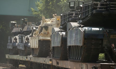M1 Abrams tanks and other armored vehicles sit atop flat cars in a rail yard in Washington.